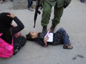 Exemple de manipulation : Un soldat israélien pointe son arme sur une jeune fille à terre.