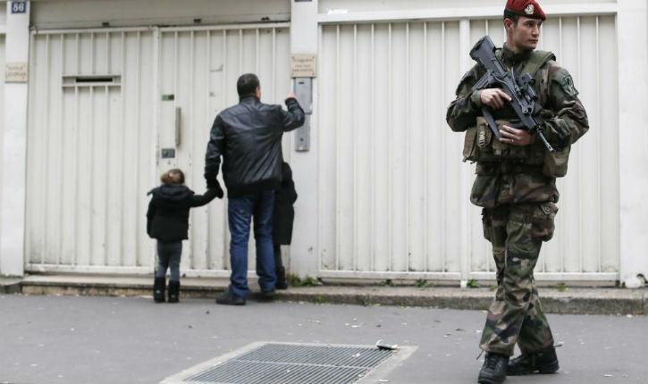 Menacés par une arme devant un collège juif, des soldats arment leur fusil d'assaut