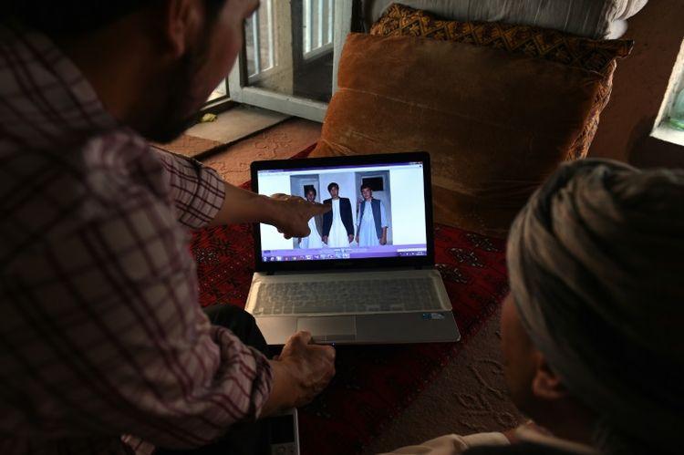 Un Afghan regarde sur son ordinateur la photo de son cousin enrôlé par l'Iran pour combattre en Syrie, le 28 juillet 2015 à Kaboul (Photo WAKIL KOHSAR. AFP)