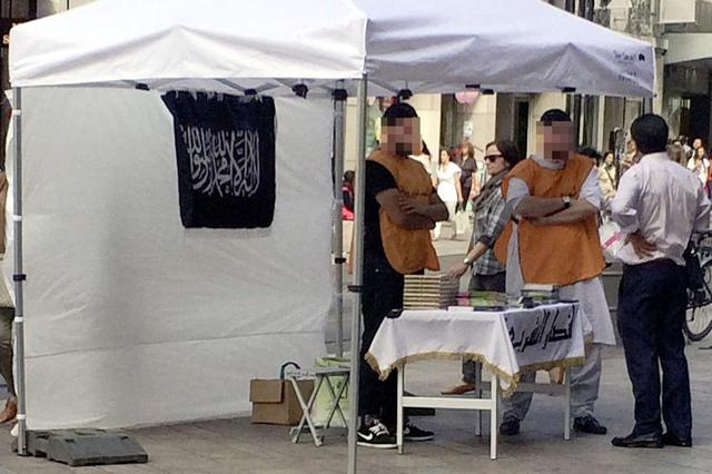 Des islamistes distribuent des Corans sur un stand arborant le drapeau de l'Etat islamique