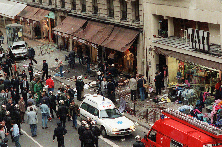 Policemen search for evidence on the site of the bomb blast in Rue de Rennes on September 17, 1986 in front of Tati store. Between December 7, 1985 and September 17, 1986, eleven terrorist bomb explosions took place in Paris, killing thirteen people and injuring 255 others, implicating the Hezbollah and the Iranian government itself.