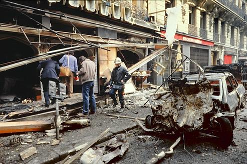 People walk past the wreckage of the bombed car that exploded the day before in Rue Marbeuf, near Champs Elysées in Paris on April 23, 1982 in front of the office of lebanese pro-irakian publication Al Watan al Arabi, causing one dead and 63 wounded. The attack is attributed to Ilich Ramirez Sanchez, aka Carlos the Jackal.