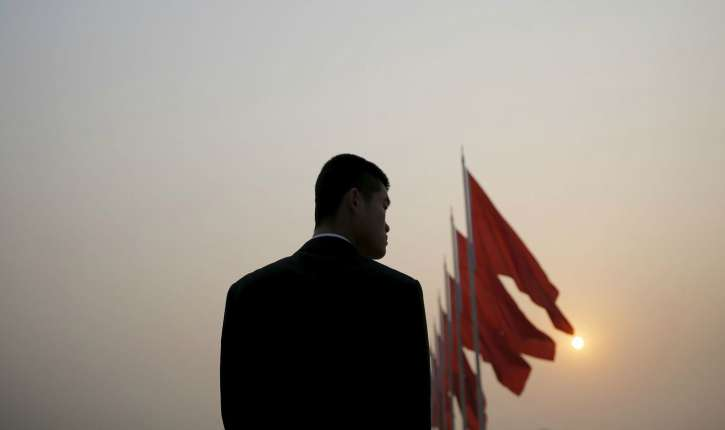 a-security-agent-stands-guard-near-the-great-hall-of-the-people-as-the-sun-appears-through-smog-ahead-of-the-closing-ceremony-of-china-s-national-people-s-congress-in-beijing_5883417