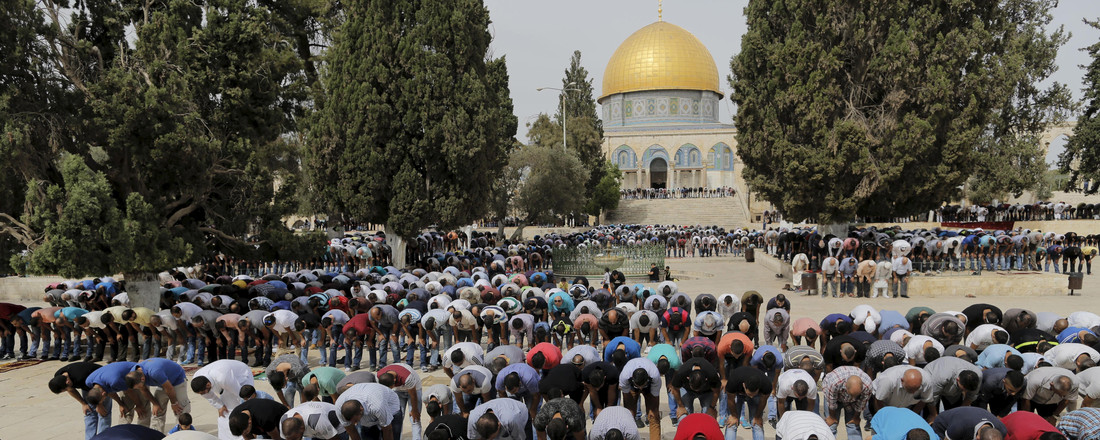 The Dome of the Rock is seen in the background as Palestinian men take part in Friday prayers in Jerusalem's Old City
